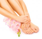 Relaxing manicure and pedicure with a pink orchid flower — Stock Photo