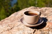 Cup on big stone over nature background — Stock Photo