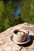 Tea with chamomile on old big stone. — Stock Photo