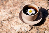 Tea with chamomile on old big stone. — Stock Photo