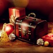 Chest, gifts and other christmas decoration on old wooden table — Stock Photo #55701157