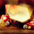 Opened chest with light, gift and other christmas decoration on old wooden table — Stock Photo #55701163