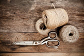 Old scissors and skein jute on wooden table — Stock Photo