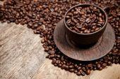 Filiżanka kawy z ziaren kawy na drewnianym stole — Zdjęcie stockowe
