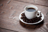 Coffee cup and saucer on wooden table — Stock Photo