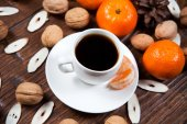 Cup of coffee with tangerines and walnut — Stock Photo