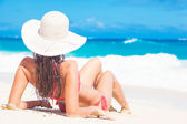 Back view of long haired girl in bikini and straw hat on tropical caribbean beach — Stock Photo