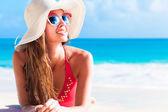Long haired girl in bikini and straw hat on tropical caribbean beach — Stock Photo