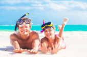 Cheerful happy couple having fun snorkeling, lying on summer beach sand with snorkel equipment — Stock Photo