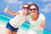 Closeup of happy young caucasian couple in sunglasses smiling on beach — Stock Photo