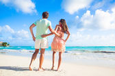 Panoramic view of happy young couple in sunglasses in bright clothes flirting on tropical beach — Stock Photo