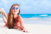 Long haired young woman in bikini and sunglasses on tropical beach — Stock Photo