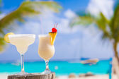 Two perfect cocktails pina colada and margarita with cherry on top, beach background — Stock Photo