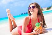 Young woman in swimsuit and straw hat in sunglasses with coconut on beach — Stock Photo