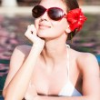 Beautiful young woman in sunglasses with flower in hair smiling in luxury pool — Stock Photo #63611293