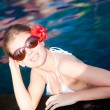 Beautiful young woman in sunglasses with flower in hair smiling in luxury pool — Stock Photo #63611303