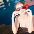 Beautiful young woman in sunglasses with flower in hair smiling in luxury pool — Stock Photo #63611313