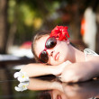 Beautiful young woman in sunglasses with flower in hair smiling in luxury pool — Stock Photo #63611337