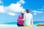 Back view of couple sitting on a tropical beach in Barbados — Stock Photo