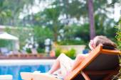 Beautiful young woman with flower in hair relaxing on sun lounger near pool — Stock Photo