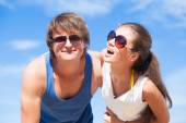 Portrait of happy young couple in sunglasses having fun on tropical beach. Thumbs up — Stock Photo