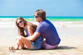 Front view happy young couple in bright clothes in sunglasses hugging on beach — Stock Photo