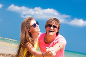 Front view of happy young couple on beach smiling and hugging — Stock Photo