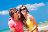 Portrait of happy young couple in sunglasses having fun on tropical beach — Stock Photo