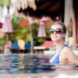 Beautiful young woman in sunglasses with flower in hair smiling in luxury pool — Stock Photo #68419803