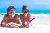 Beach travel couple having fun snorkeling, lying on summer beach sand with snorkel equipment — Stockfoto