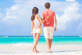 Back view of happy young couple on the beach — Stock Photo