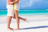 Legs of young hugging couple on tropical turquoise beach — Stock Photo