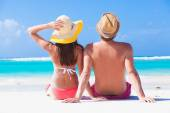 Happy young couple in hats sitting on a tropical beach in Barbados — Stock Photo