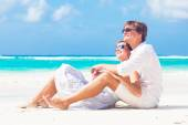 Back view of happy young couple in white on the beach — Stock Photo