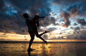 Sunset silhouette of young couple in love hugging at beach — Stockfoto