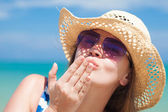 Long haired girl in a hat and sunglasses on tropical thailand beach blowing air kiss — Stock Photo