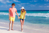 Happy romantic young couple holding hands walking at the beach — Stockfoto