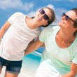 Closeup of happy young caucasian couple in sunglasses smiling on beach and looking at sun — Stok fotoğraf #76631933