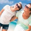 Mutlu genç çift sahilde gülümseyen ve güneşe bakarak güneş gözlüğü closeup — Stok fotoğraf #76631933