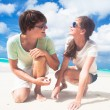 Closeup of happy young caucasian couple in sunglasses smiling on beach and looking at sun — Stok fotoğraf #76632025