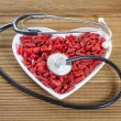 Goji berries in the shape of a heart with a medical stethoscope — Stock Photo #56465323