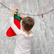 Boy hangs socks for Santa Claus. — Stock Photo #56465497