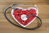 Goji berries in the shape of a heart with a medical stethoscope — Stock Photo