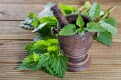 Fresh nettle leaves with a mortar on a wooden background — Stock Photo