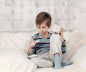 Boy drinking tea and eating biscuits. Toned image. — Stock Photo