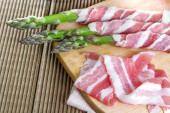 Bacon and asparagus on a wooden background — Stock Photo
