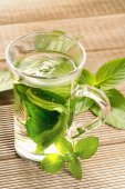 Mint tea with fresh mint leaves on a wooden background — Stock Photo