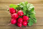Fresh radishes on a wooden table — Stock Photo