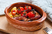 Octopus baked with tomatoes and potatoes — Stock Photo