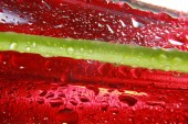 Shiny water drops sprayed on textured red surface. — Stockfoto